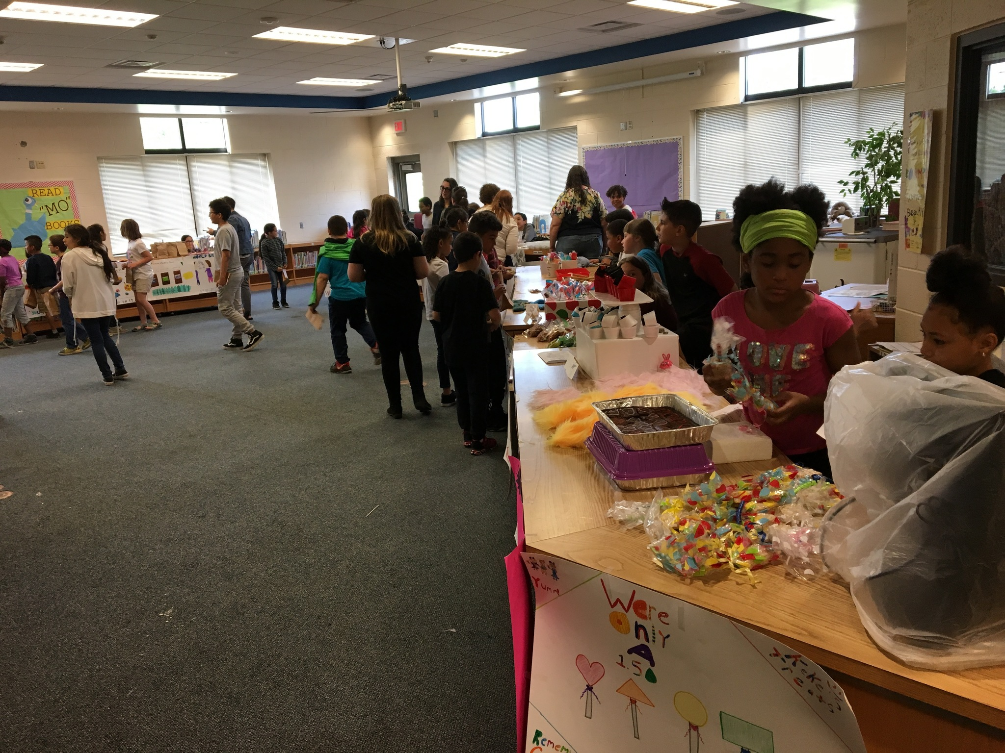 students in the library selling their creations for Market Day